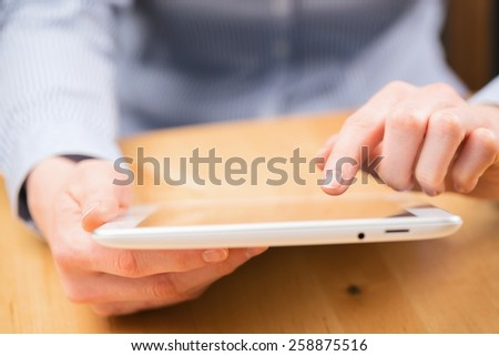 A young woman about to perform a hand gesture on a tablet screen. Closeup image over a wooden desktop with shallow DOF - focus on the index finger. - stock photo