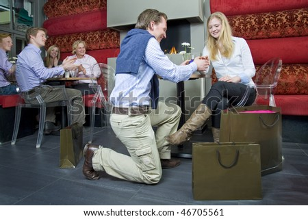 A young woman accepting her boyfriends proposal, whilst the other guests at a restaurant applaud the young couple - stock photo