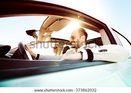 A young woman and a young man are laughing in the car, enjoying in the road trip - stock photo
