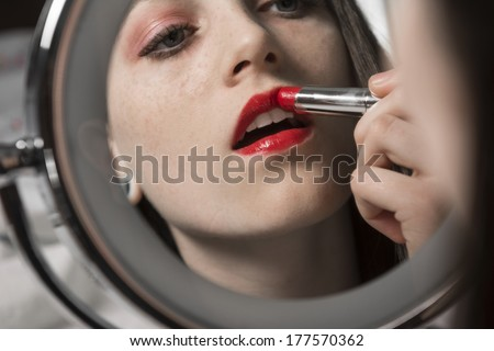 A young woman applies red lipstick in makeup mirror