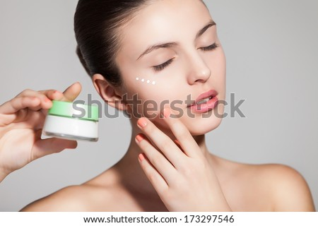 A young woman applying anti-wrinkle cream - stock photo