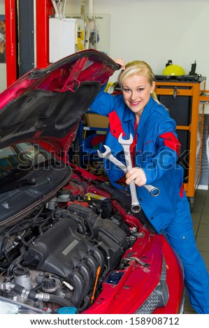 a young woman as a mechanic in a garage. rare professions for women. car is being repaired in the workshop - stock photo