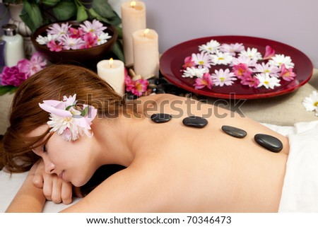A young woman at a spa waiting for a massage with hot stones on her back. - stock photo