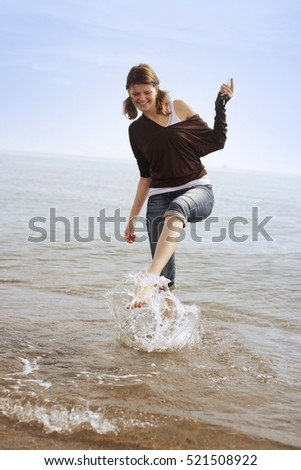 A young woman at the beach, splashing in the surf.