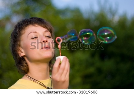 A young woman  blowing up soap-bubbles on the green trees background