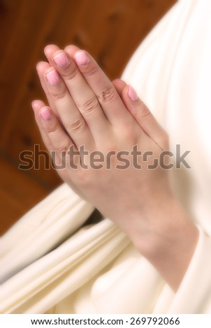 A young woman brings her hands together in prayer to the almighty father in heaven. - stock photo