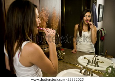 A young woman brushing her teeth at the bathroom sink - stock photo