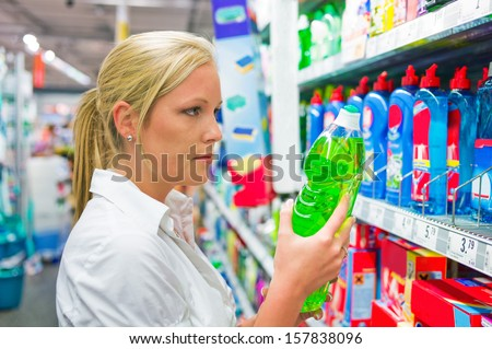 a young woman buys cleaning products for cleaning in a supermarket.