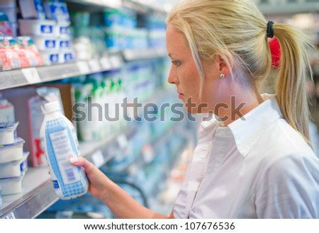 a young woman buys milk at the supermarket. stands in front of the refrigerated section. - stock photo