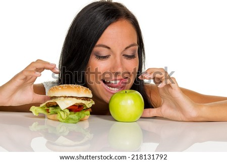 a young woman can not decide between a hamburger and an apple is. healthy or unhealthy diet.