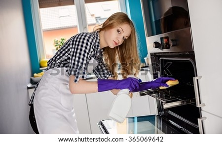 A young woman cleans the oven. Rubber gloves on her hands. Using cleaning fluid and sponge. Dressed in a plaid shirt and white apron - stock photo