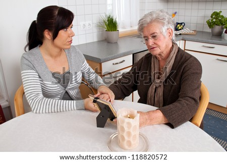 a young woman comforting a widow after death. bereavement support. - stock photo