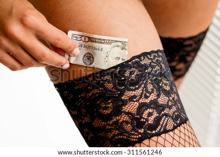 a young woman dies a dollar money bill in her stocking. symbolic photo for prostitution - stock photo