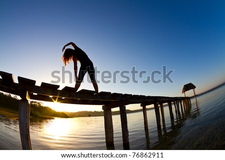 A young woman does her early morning exercises while enjoying a Guatemala Dawn over lake Peten. - stock photo