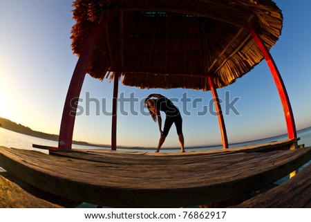A young woman does her early morning exercises while enjoying a Guatemala Dawn over lake Peten.