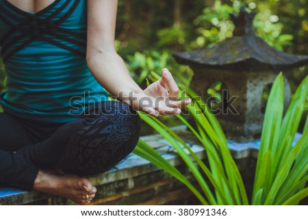 A Young woman doing meditation outdoors in tranquil environment - stock photo