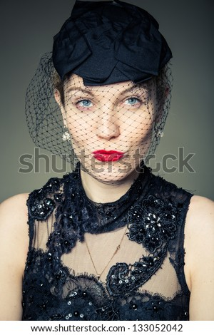 A young woman dressed in black in a scenario as a widow. - stock photo