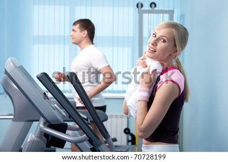 A young woman drying sweat with a towel in gym - stock photo