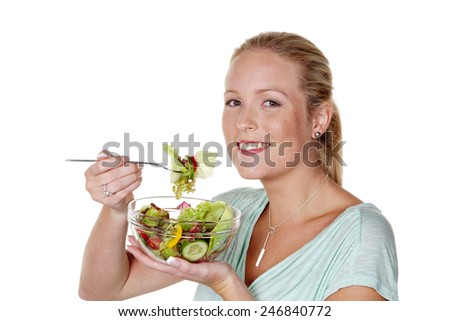 a young woman eating a crunchy salad at lunch time. healthy diet with vitamins - stock photo