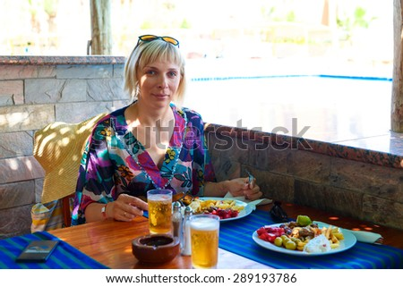 A young woman enjoying a meal and beer - stock photo