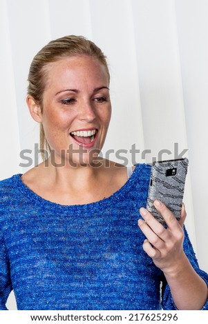 a young woman enjoying a text message she received on her cell phone. - stock photo