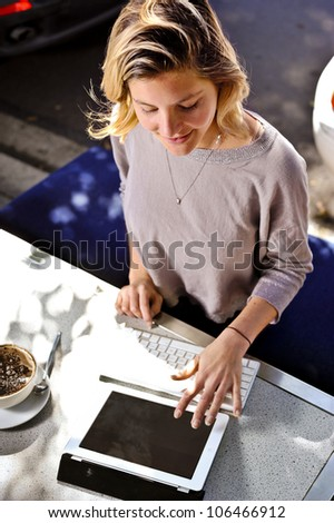a young woman enjoys her cappuccino whilst browsing the internet - stock photo