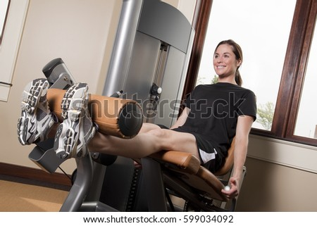 A young woman exercising with the leg extension machine.