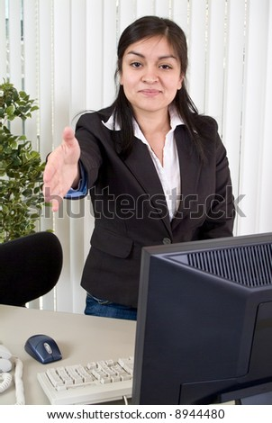 A young woman extending her hand in a posture of greeting or welcoming someone. - stock photo