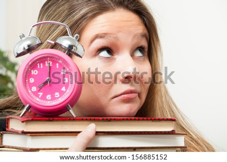 A young woman frowns and rolls her eyes upwards, wondering how she will be able to complete homework she has to finish - stock photo