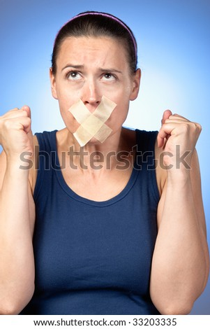 A young woman frustrated at being prevented from saying something - stock photo