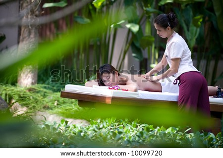 A young woman gets a massage outside in a tropical environment