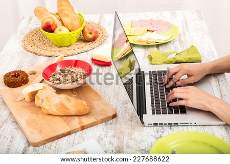 A young woman having breakfast while using a laptop computer.  - stock photo