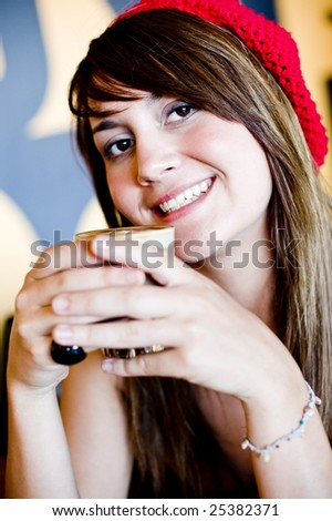 A young woman having coffee in a cafe - stock photo