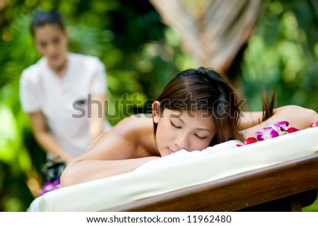 A young woman having massage outside in tropical garden - stock photo