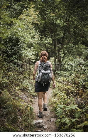 a young woman hiking on a worn path - stock photo