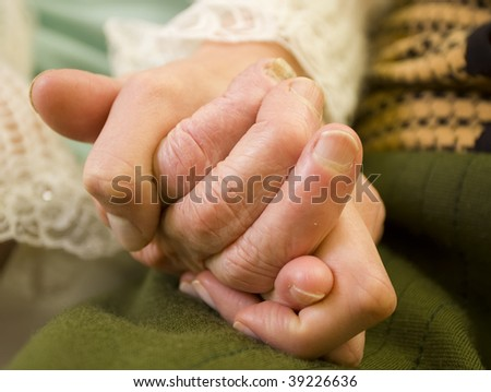 A young woman holding a senior woman's hand.