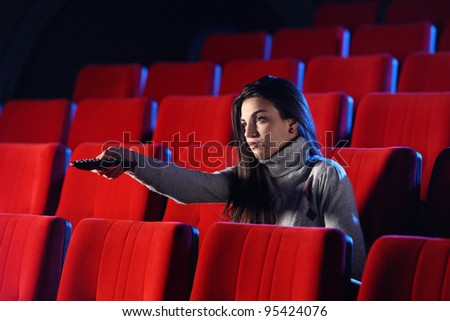 a young woman holding a TV remote control, in the background you can see the red chairs in a movie theater. conceptual image - stock photo