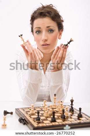 a young woman holding chess pieces, looking at camera