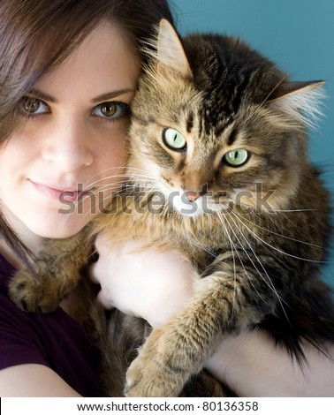 A young woman holding her pet Maine Coon cat. - stock photo