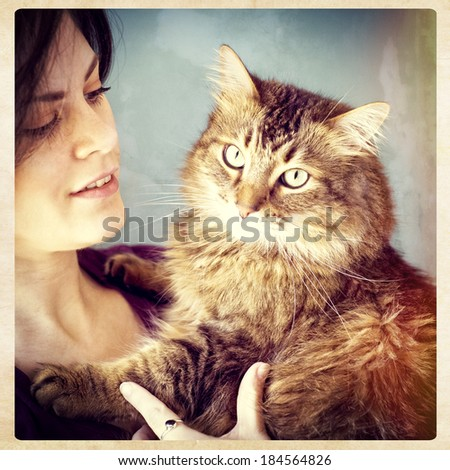 A young woman holding her pet Maine Coon cat, instagram style - stock photo