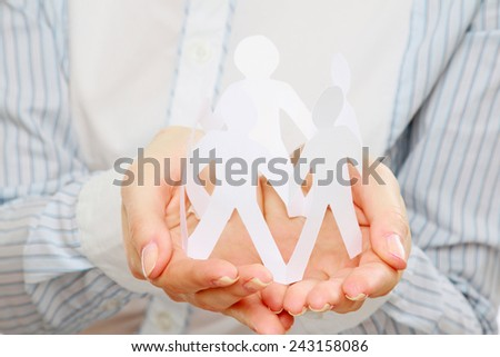 A young woman holding paper people - stock photo