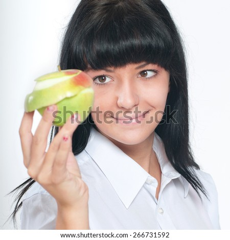 A young woman holding pilled apple