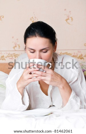 A young woman holding white a cup of coffee on bed at bedroom