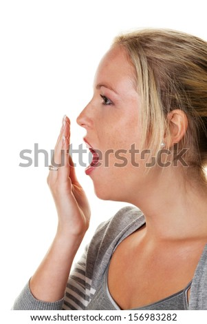 a young woman holds her hand to her yawning mouth. fatigue and lack of sleep - stock photo