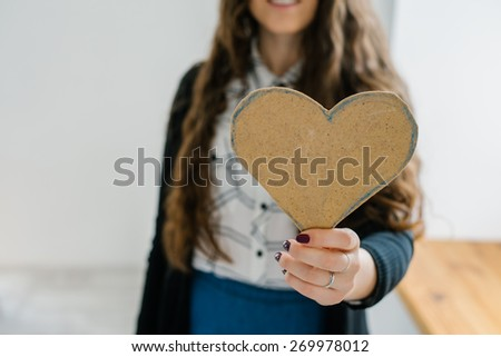 A young woman holds out a cut out construction paper heart near the window. - stock photo