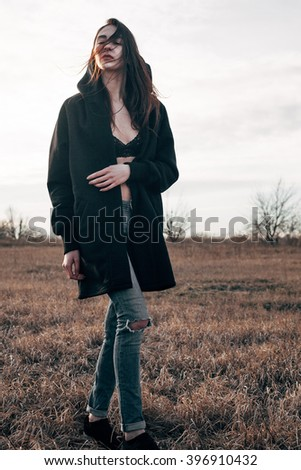 A young woman in a black coat walking on the field. Wind