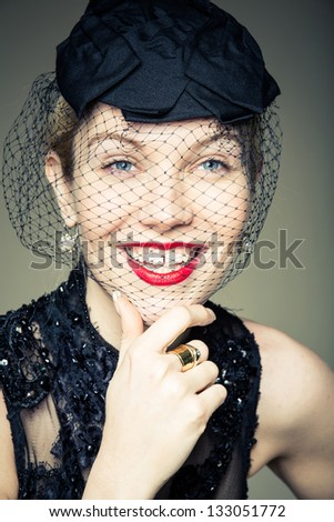 A young woman in a black veil smiling - stock photo