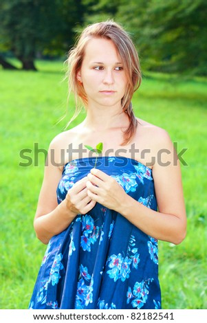 A young woman in a blue dress with a small plant in the hands - stock photo