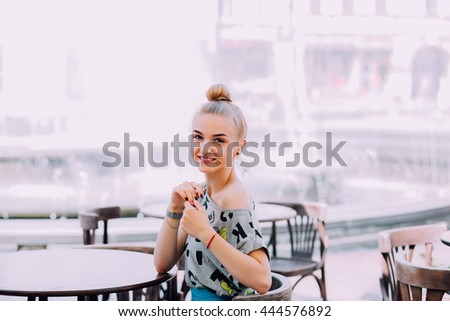 A young woman in a cafe at an empty table.  Concept expectations. Film processing.