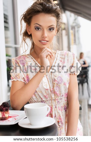 A young woman in a cafe. Outdoors - stock photo
